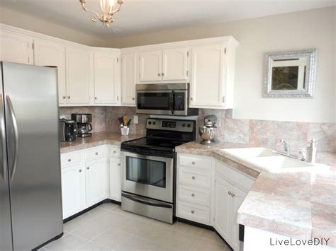 white wooden kitchen cabinet with many drawers plus marble counter top and silver black
