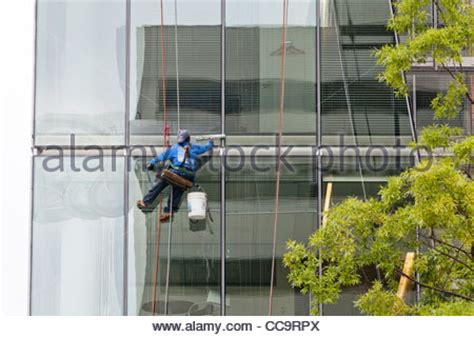 bosuns chair window cleaning high rise window cleaner sitting in a bosun s chair usa