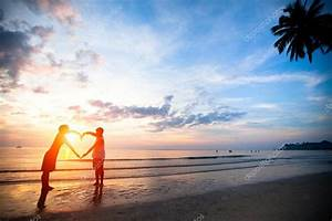 Young couple holding hands heart-shaped on the sea beach ...
