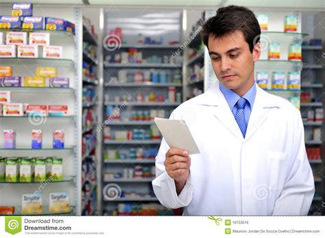 pharmacy ls for reading pharmacist reading prescription at pharmacy stock photo
