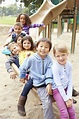 Group Of Young Children Sitting On Slide In Playground ...