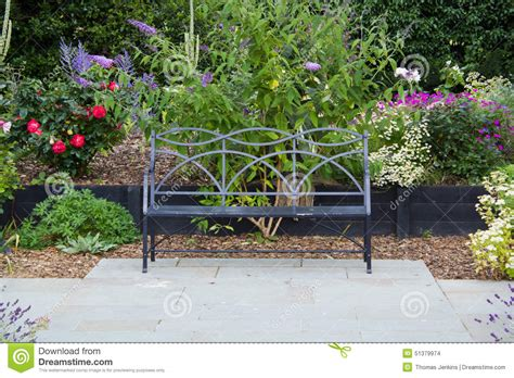 bench seat on garden patio with flowers stock photo