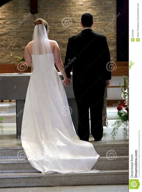 young couple holding hands  altar  wedding day royalty  stock  image