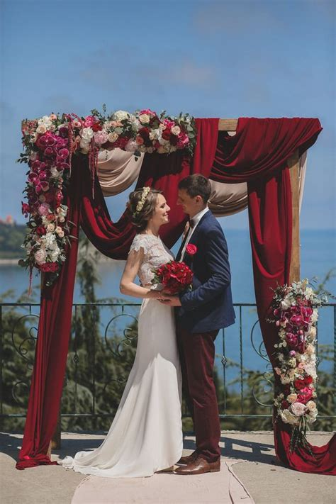 Picture Of A Gorgeous Wedding Arch With Burgundy Draperies