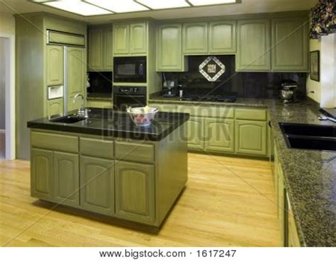 picture or photo of modern kitchen with green stained cabinets granite counters wood flooring
