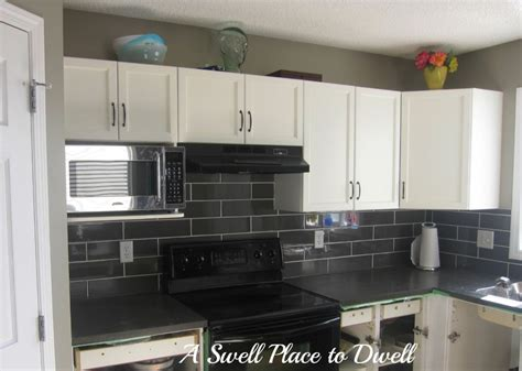 Black Backsplash Tile : White L Shaped Cabinetry With Granite Countertop With Grey