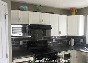 White l shaped cabinetry with granite countertop with grey for Kitchen colors with white cabinets with subway wall art
