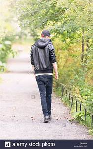 Young man walking away on footpath in a park Stock Photo ...