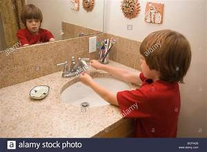 A Seven Year Old Boy Washing His Hands With Soap In The