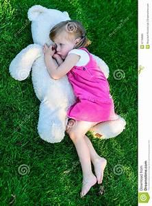 Sad Little Girl Lying On Grass With Large Teddy Bear Stock ...