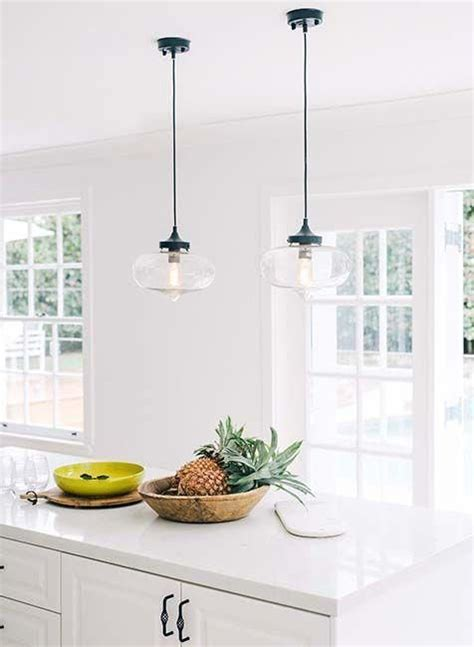 Industrial hanging pendant lights over the white granite