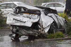 A Smashed Car Sits In The Carpark Of A Shopping Centre In