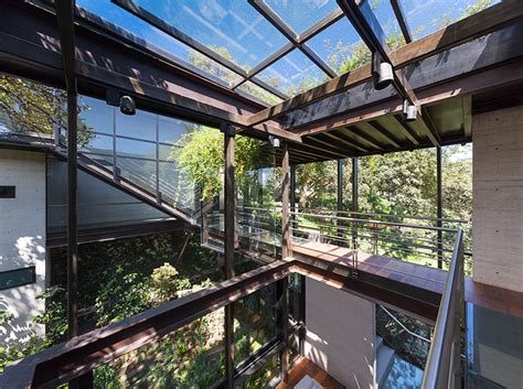 outdoor elevated glass walkway connects  sections  house
