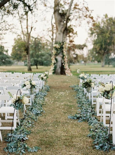 greenery lined aisle at outdoor wedding ceremony outside