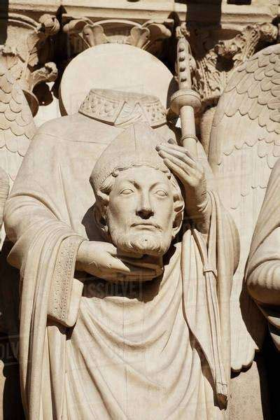 statue  st denis holding  head   notre dame