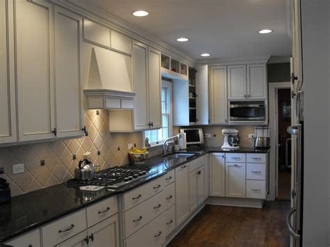 black quartz countertop kitchen featuring white painted cabinets contrasting with