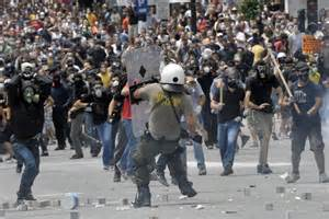 A huge crowd of protesters race towards a riot policeman ...