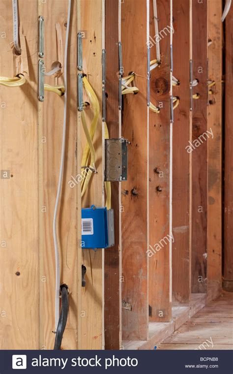 many electrical wires running through wall studs and