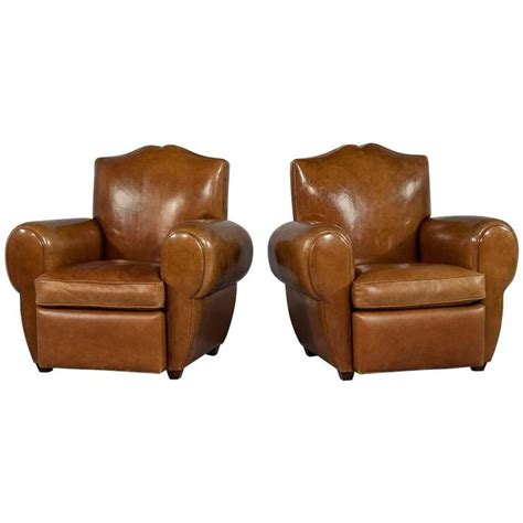 pair of distressed brown leather deco club chairs at