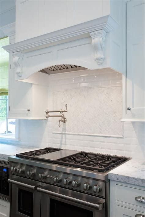 gorgeous kitchen features  white curved range hood