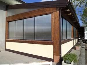 Pannelli scorrevoli frangivento in policarbonato trasparente posti sopra a muretto in legno