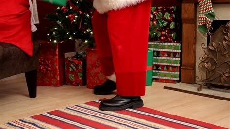Santa Claus Putting Gifts Under Christmas Tree Stock