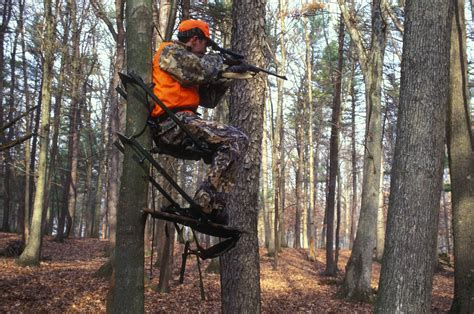 File:Hunter holds his eye to the scope of his gun while ...