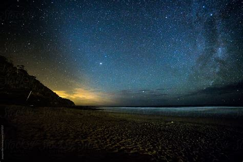 Stars over a beach with lights afar by Joaquim Bel - Milky