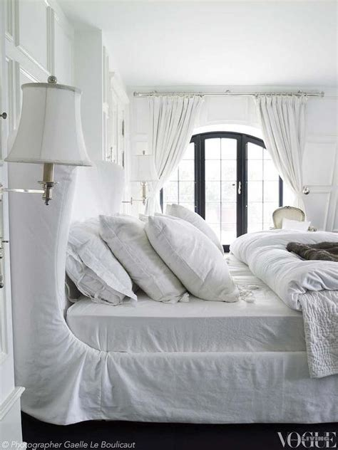 white slipcovered white wingback bed with slipcover transitional bedroom
