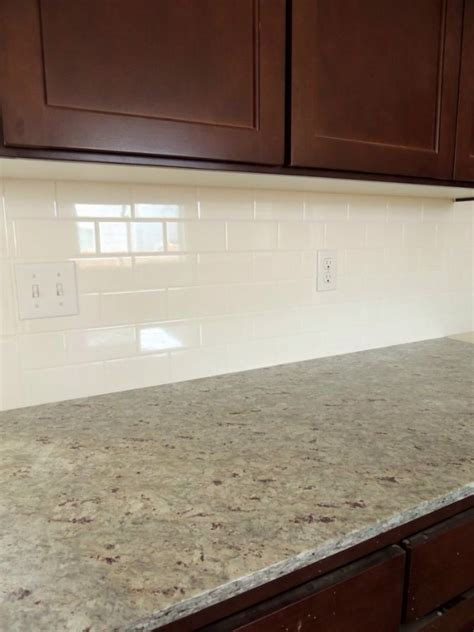 Dark cabinets with light granite counters and white subway