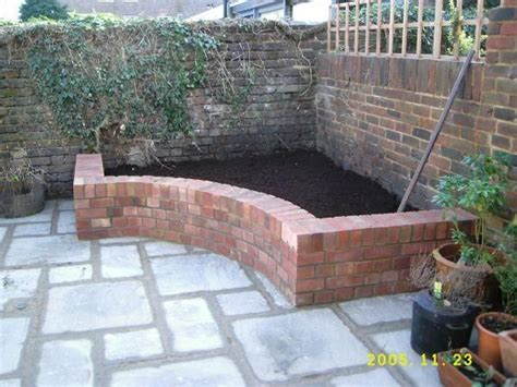 raised brick garden bed tucks away in a corner the curve