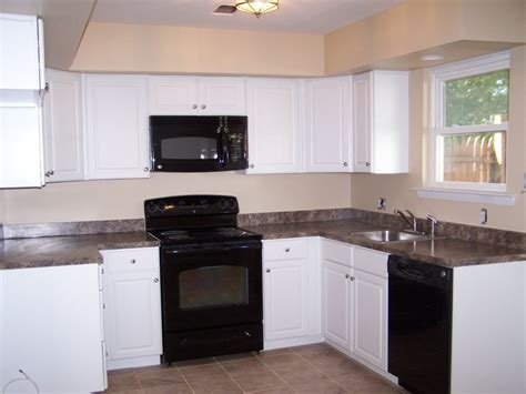 kitchens with white cabinets and black appliances black and white kitchen cabinets 9861