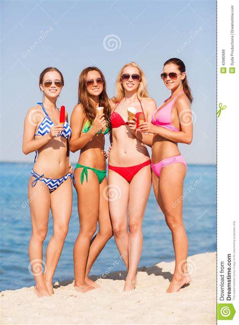 Group Of Smiling Women Eating Ice Cream On Beach Stock