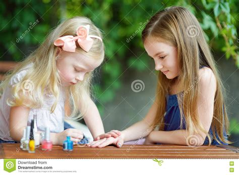 Adorable Little Girls Having Fun Playing At Home With Colorful Nail Polish Doing Manicure And