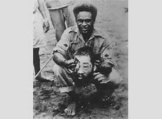 Jacob Vouza displays head of a Japanese soldier at