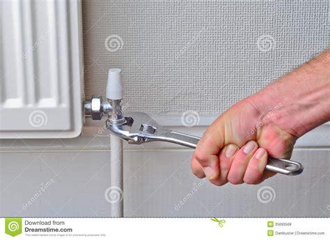 plumber repairing  radiator pipe royalty  stock