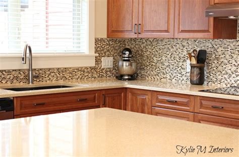 Ideas For Kitchen Countertops And Backsplashes - cream quartz countertops cherry kitchen cabinets small mosaic tile backsplash cable knit