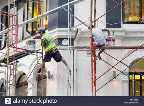 due uomini su una impalcatura  lavorare  condizioni