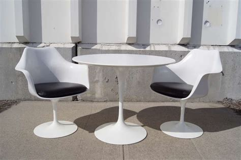pair of tulip armchairs and tulip dining table by eero