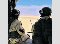 A DEVGRU and a Delta Force operator ride in a combat