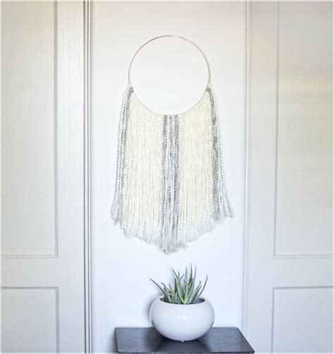 Underneath is a whitewashed shelf with three small black metallic lanterns and two canning jars with flowers in them. Top 10 Simple Yet Amazing DIY Fiber Wall Art - Top Inspired