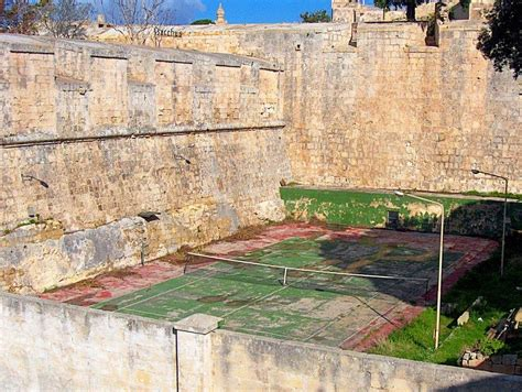 neglected tennis court beneath  ancient walls  mdina urban ghosts media