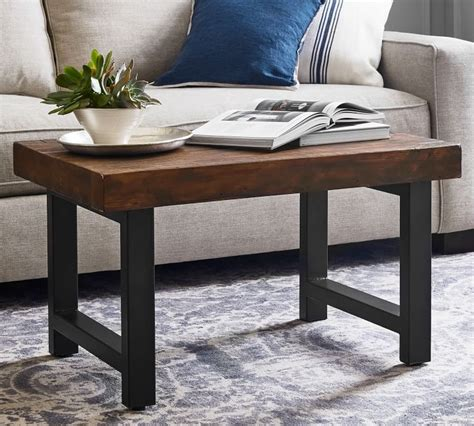 Heavy wrought iron forms a linear base that looks warm against natural wood. Griffin Small Space Reclaimed Wood Coffee Table | Pottery Barn