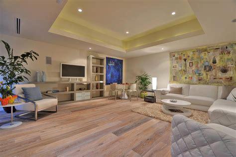 Mediterranean Kitchen Ideas - white washed oak flooring family room modern with armchair art installation art