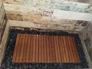 Teak wood shower floor surrounded by river rock walls for Teak tiles bathroom