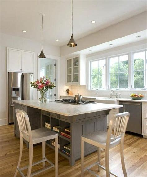 Kitchen With Both Peninsula And Island by Open And Airy Kitchen With Seating Around A Cooktop