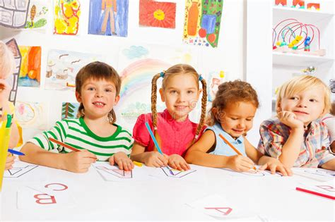 boys and drawing letters in writing lesson stock 331 | boys girls drawing letters writing lesson group diverse looking children kindergarten class early reading class 47926541