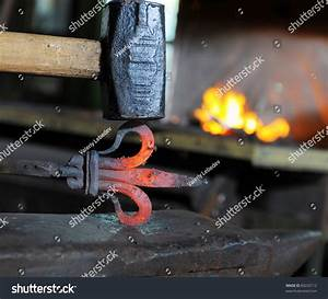 Blacksmith Forges A Red-Hot Iron In The Forge Stock Photo ...