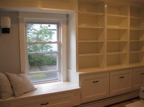 White Wooden Bookshelves Beside White Wooden Window Seat
