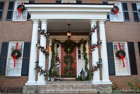 decorating porch columns for christmas front porch decorated for christmas with three wreaths on door and pottery barn knock off garland